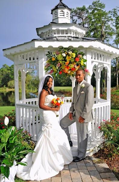 Noivo negro com traje cinza e sua noiva negra em frente ao coreto. Foto: Calvin Bolden Photography.