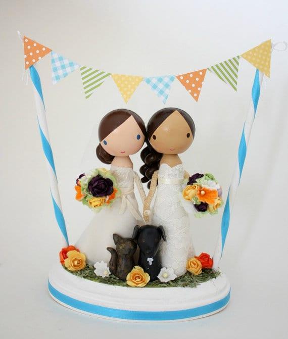 Noivinhas de topo de bolo em madeira da Lollipop Workshop. Noivas homossexuais com bandeirinhas.
