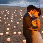 Casamento na praia Tabi e Carlos: noivos na areia com velas de noite em luau. Foto: André Pinnola