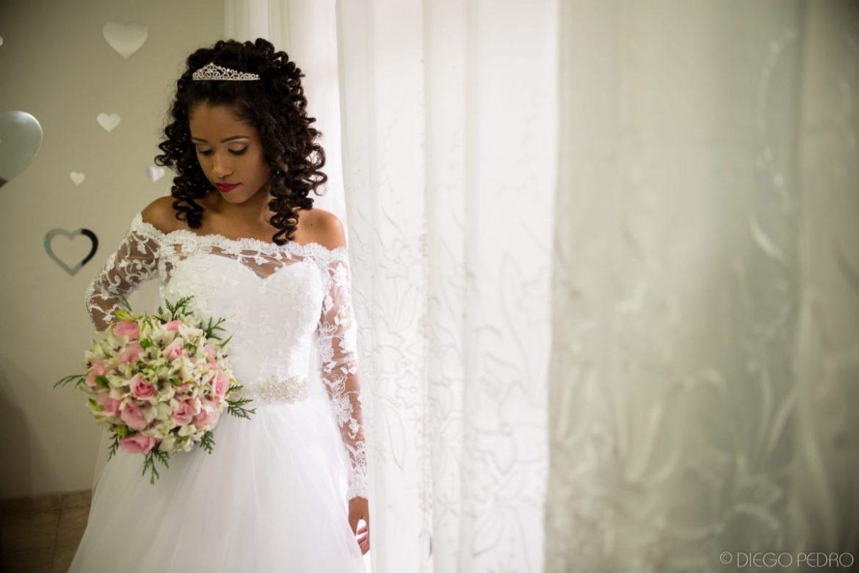 Noiva negra de cabelo cacheado solto. Vestido de noiva com manga comprida. Noiva de cabelo cacheado. Casamento Naara e Rodrigo. Foto: Diego Pedro.