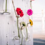Decoração de casamento com flores (gérberas) em garrafinhas de vidro transparente. Decoração pela florista Lygia de Luca, da Leve Flores. Foto: GMeira Fotografia.