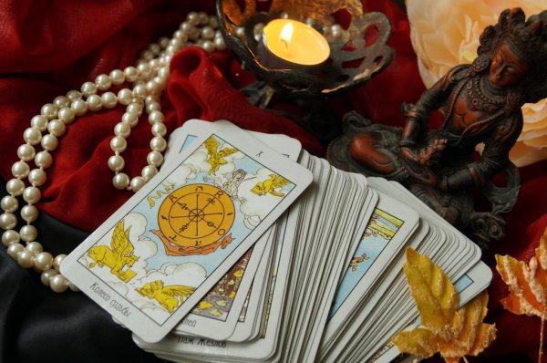 Mesa de Tarot com a carta de Tarot A Roda da Fortuna 10 por cima das cartas, vela, colar de pérolas e Buda
