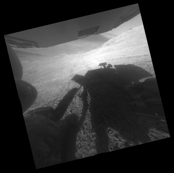 View from the Opportunity rover looking downhill from the steep hillside on sol 4323 (March 22, 2016). Part of the floor of Endeavour crater can be seen beneath the underside of one of the solar panels. Image Credit: NASA/JPL-Caltech