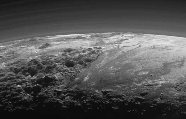 Perspective view of Pluto, showing the ice mountains and glacier-like plains, as well as haze layers in the atmosphere. Image Credit: NASA/JHUAPL/SwRI)