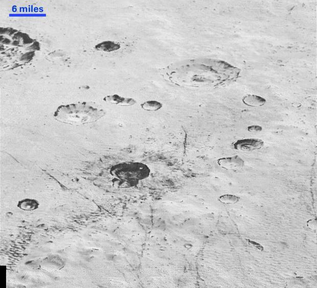 View of rugged, cratered icy plains on Pluto, within the 155-mile (250-kilometer) wide Burney Basin. Layering can also be seen inside the walls of the craters as well as dark linear features which are possibly tectonic in origin. Image Credit: NASA/JHUAPL/SwRI