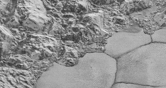 "High-resolution image of Pluto from New Horizons, showing jumbled blocks in the water ice crust, which border the smooth nitrogen ice plains, giving the appearance of a ""shoreline."" Photo Credit: NASA/JHUAPL/SwRI"