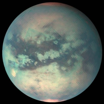 Titan, seen here in infrared to view the surface below the thick atmospheric haze, has methane fog, rain, rivers, lakes, and seas. Image Credit: NASA/JPL/University of Arizona