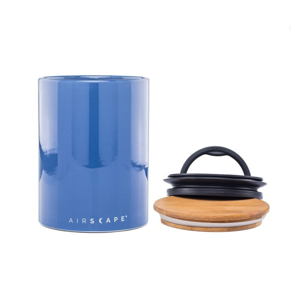 Photo of a blue ceramic coffee storage container with wooden and black plastic lids.