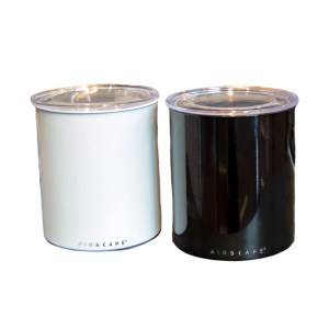 Photo of two, one kilo canisters, one white and one black, both have lids on them.