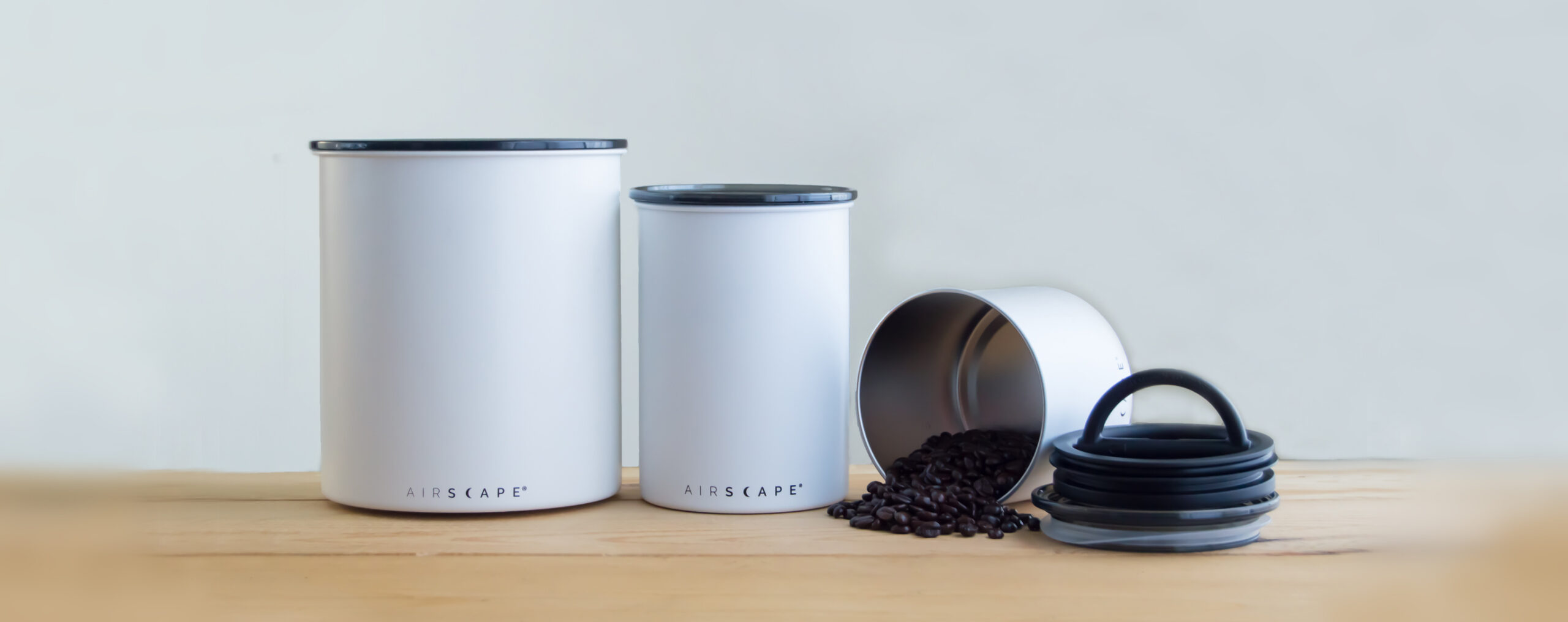 Photo of three matte white Airscape coffee storage containers in various sizes