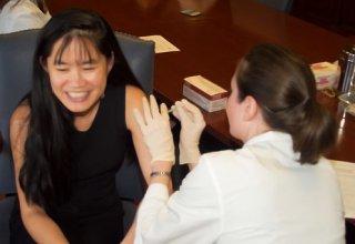 female receiving flu shot at on-site flu clinic