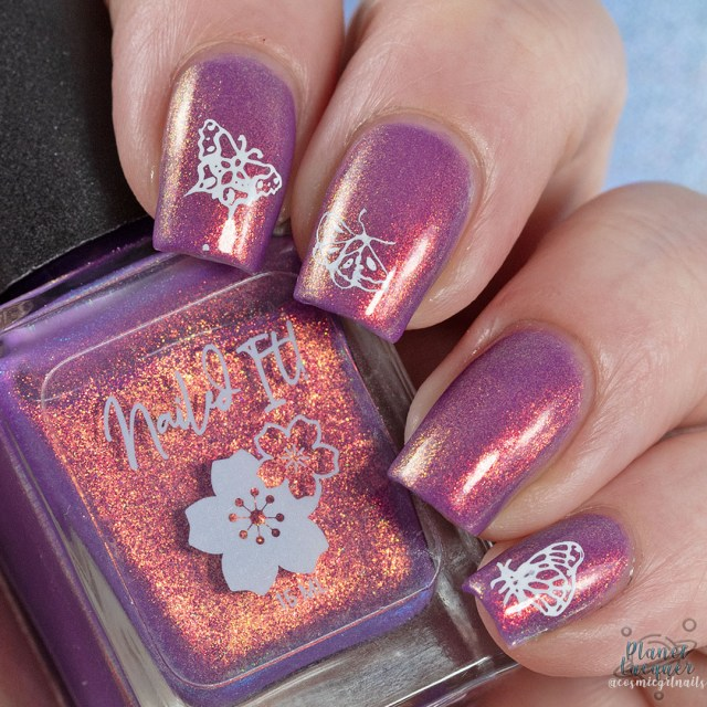 Pictured is a swatch of four fingers painted with butterfly nail art on pointer, middle and pinky by Britta in the nail polish Spotted Lady apart of the four piece Secret Garden Collection by Nailed It! Nail Polish.