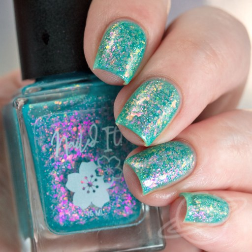 4 Finger nail swatch of Bedtime Blues a sheer turquoise jelly packed with violet/pink/gold/crystal flakies, and a touch of holo micro flakies nail polish by brand Nailed It from The Charity Box Book Club February 2021