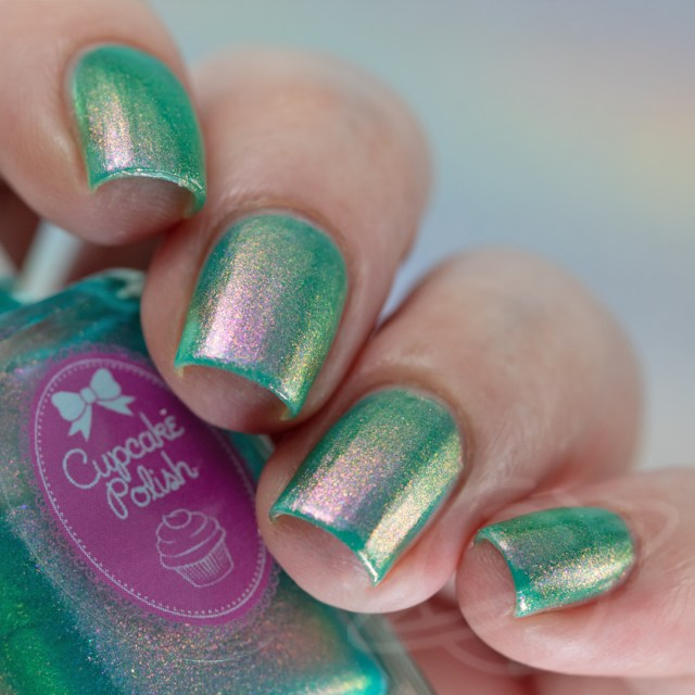 Pictured here is a four finger nail swatch of Cupcake Nail Polish Moongate a turquoise nail polish packed with pink to red to gold iridescent aurora shimmers photographed in artificial daylight bulbs