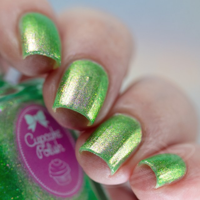 Pictured here is a four finger nail swatch of Cupcake Nail Polish Bermuda Triangle a grass green nail polish packed with purple to gold iridescent aurora shimmers photographed in artificial daylight bulbs