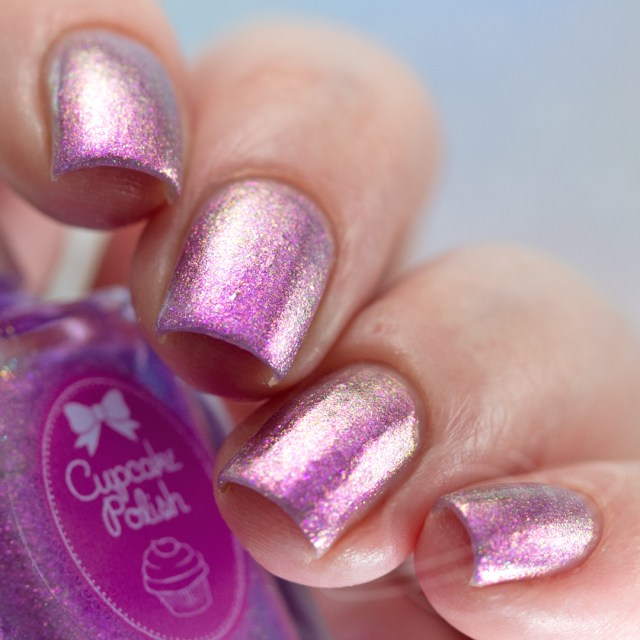 Pictured here is a four finger nail swatch of Cupcake Nail Polish St. George a light purple nail polish packed with green to gold iridescent aurora shimmers photographed in artificial daylight bulbs