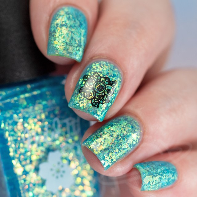 This image features a four finger swatch with the nail polish Blueberry-licious: A sky blue jelly base packed with gold/copper/green crystal flakies and a touch of holo flakies from Nailed It! Nail Polish new collection Taste the Rainbow