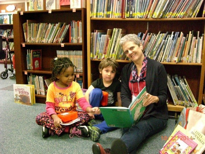 Madison Charles, Ira Stone, and GrandPal Jan Johnson enjoy a book together.
