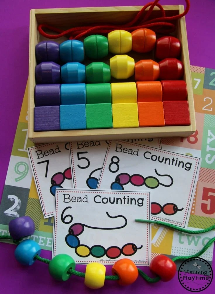 giant wooden beads with a shoelace on a table with bead pattern counting cards