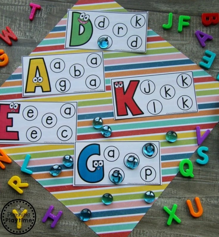 Alphabet cards with large color letter. Smaller circles with various letters. Colored marbles mark matching letters.
