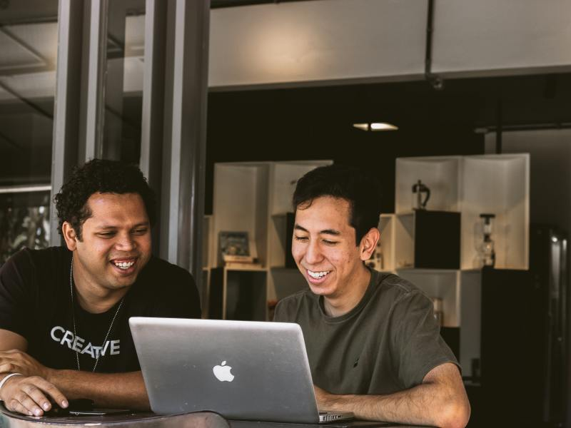 two small business owners sitting at a table in front of a laptop having a meeting