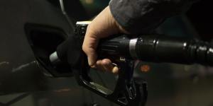 closeup image of man pumping gas into the tank of his vehicle