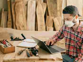 carpenter wearing a mask sitting at a worktable in his woodshop, looking up information on his laptop