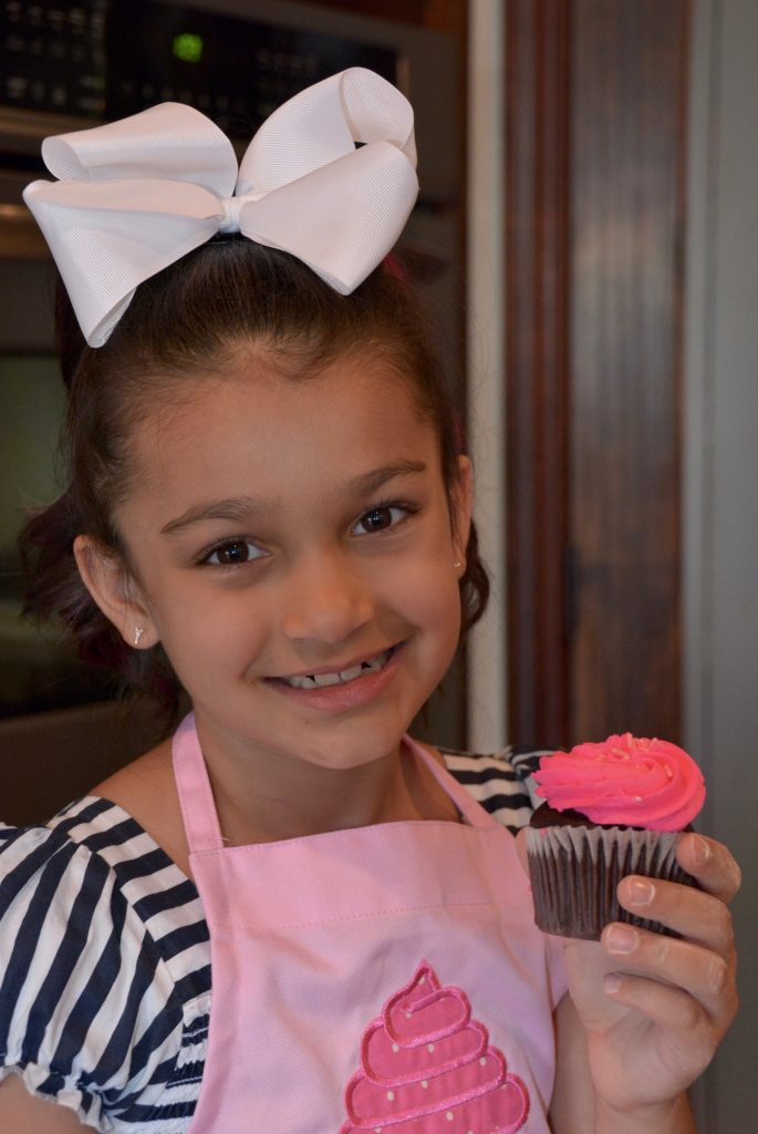 Sofina-chishti-7 child chef holding a cupcake
