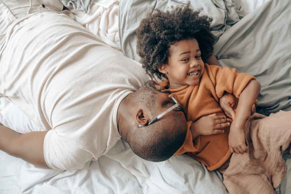 smiling african american dad and child on bed