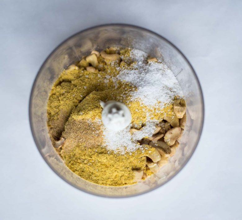 Vegan parmesan cheese ingredients in a small food processor on a white background. There are cashews, salt, nutritional yeast, garlic powder, and onion powder.