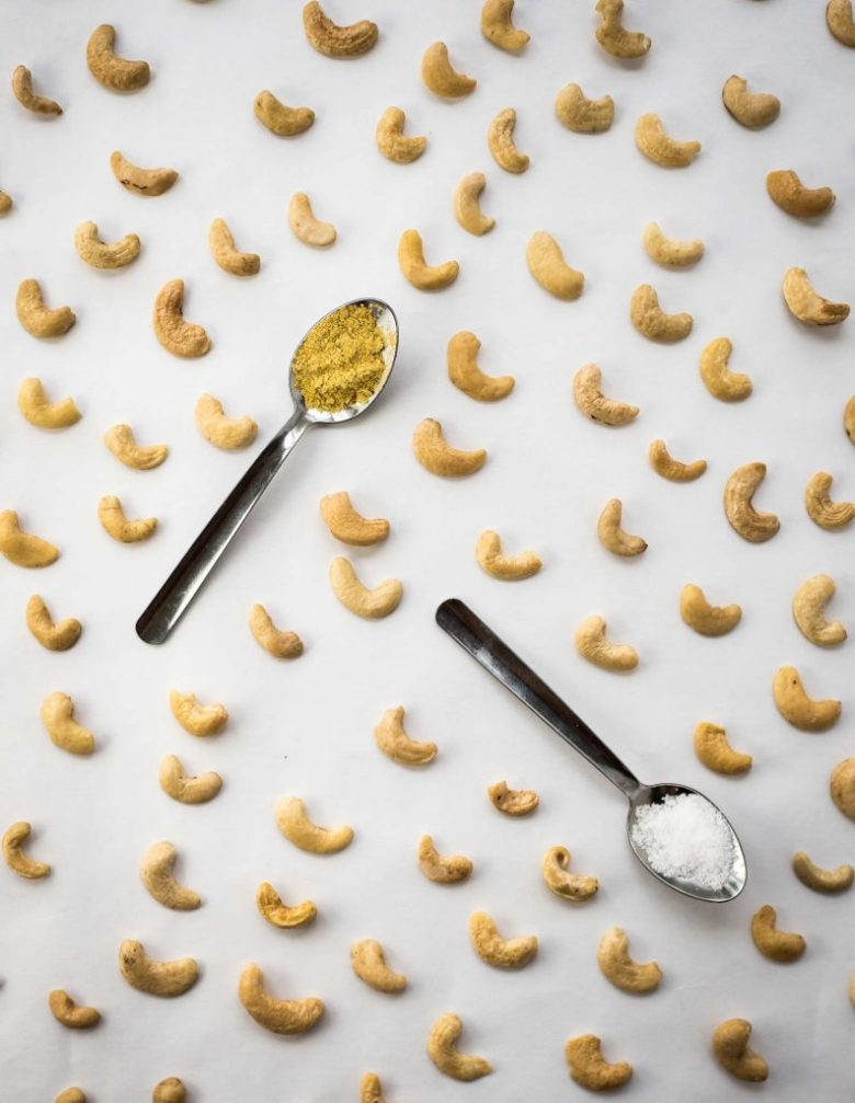 Cashews sit on a white background with two small spoons filled with nutritional yeast and salt. These are ingredients for vegan parmesan cheese.