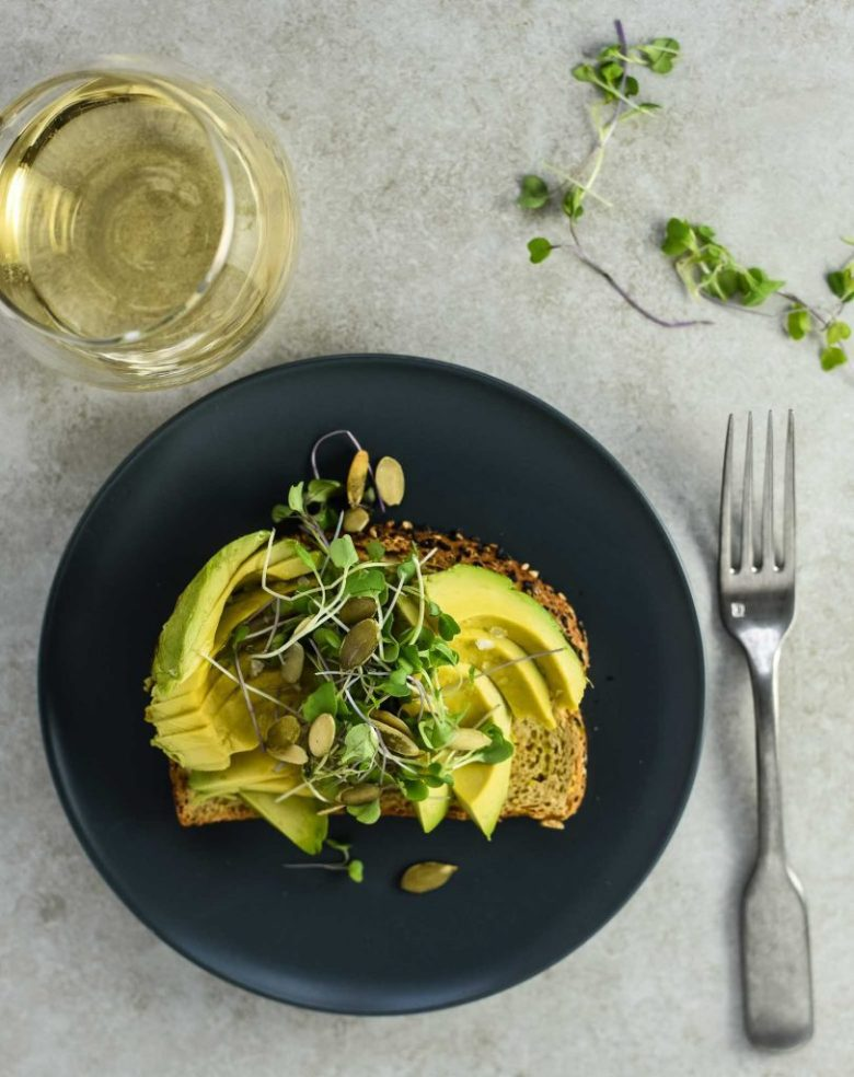 Vegan avocado toast with microgreens and pepitas on blue plate. Fork to the right of the plate and a glass of white wine to the left of the plate. The background is light textured grey.