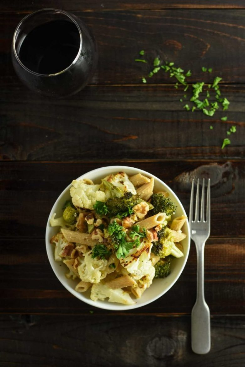 Vegan broccoli cauliflower pasta recipe in small white bowl on dark wood table. There is fork to the right of the plate and some loose parsley on the table. There is a glass of Pinot Noir in the corner.