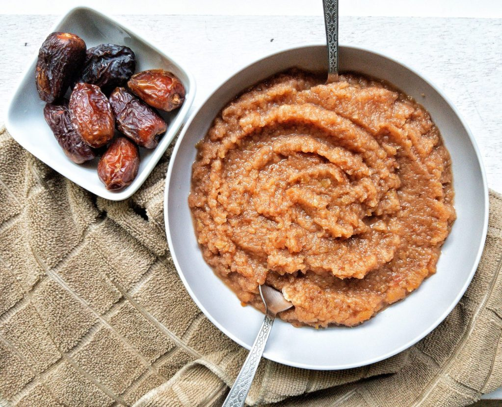 Homemade applesauce in a bowl with a side of dates