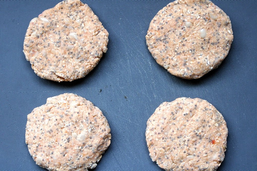 Four, uncooked vegan burger patties