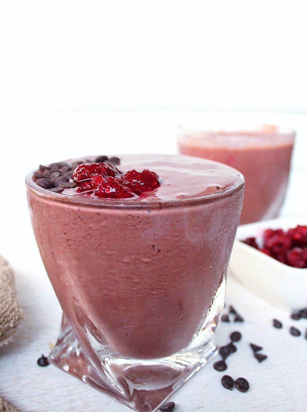 Raspberry chocolate smoothie topped with chocolate chips and raspberries