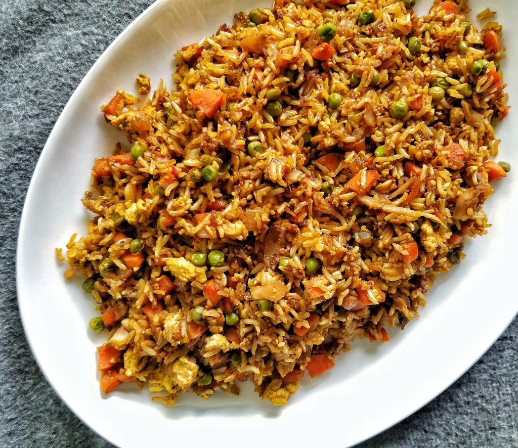 """Vegetable and tofu scramble no-oil """"fried"""" rice in a large platter."""
