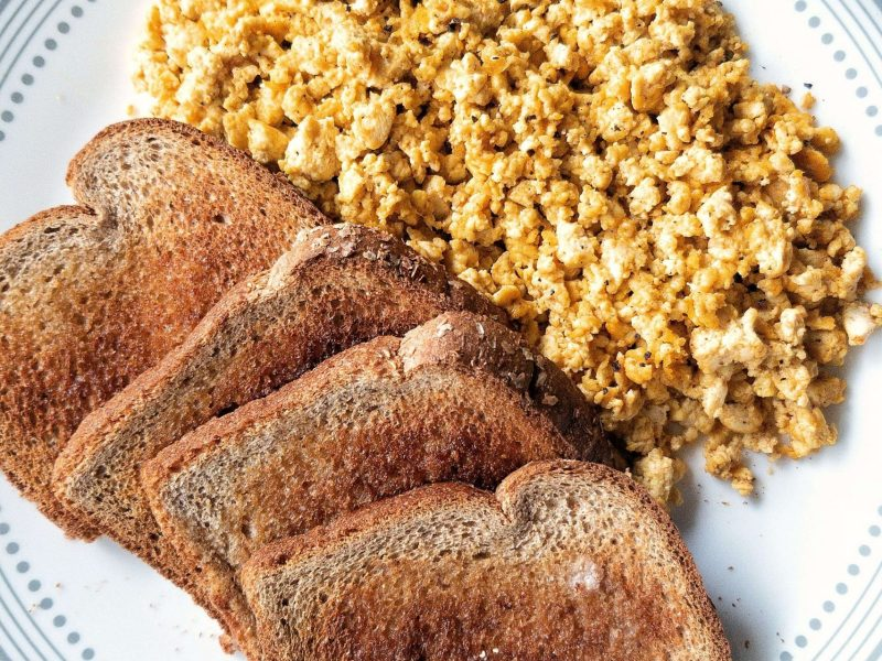 Tofu scramble with a side of buttered whole wheat toast on top of a white plate