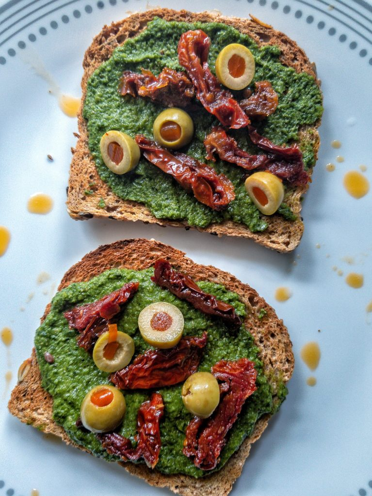 Two slices of toasted whole wheat bread topped with sliced green Spanish olives, sun-dried tomatoes- and pesto.