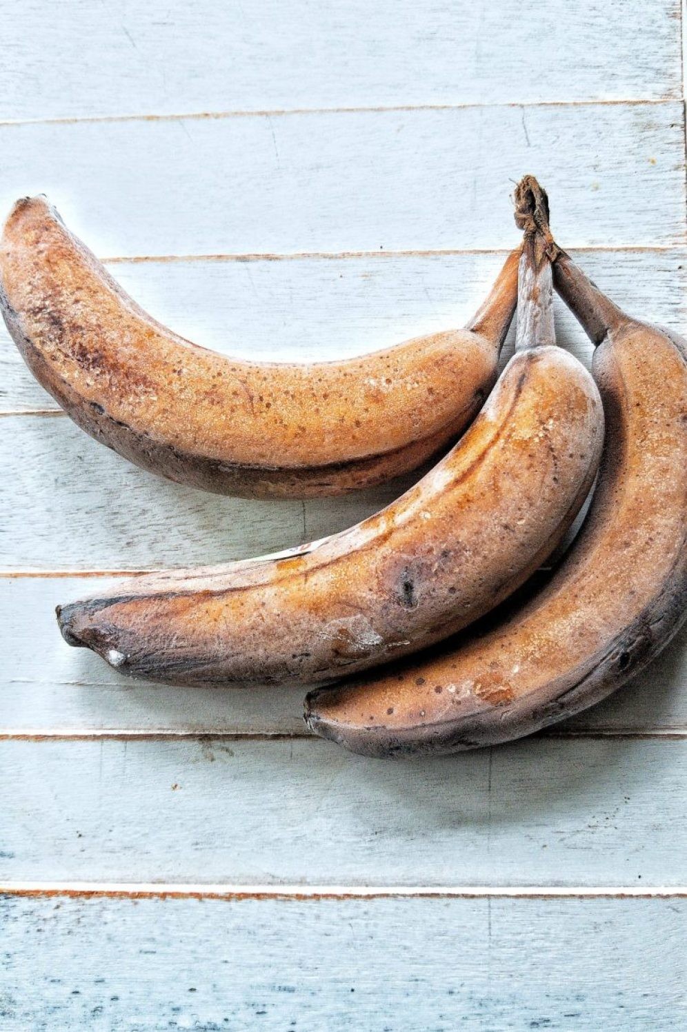 Three frozen bananas against a blue-white wooden background