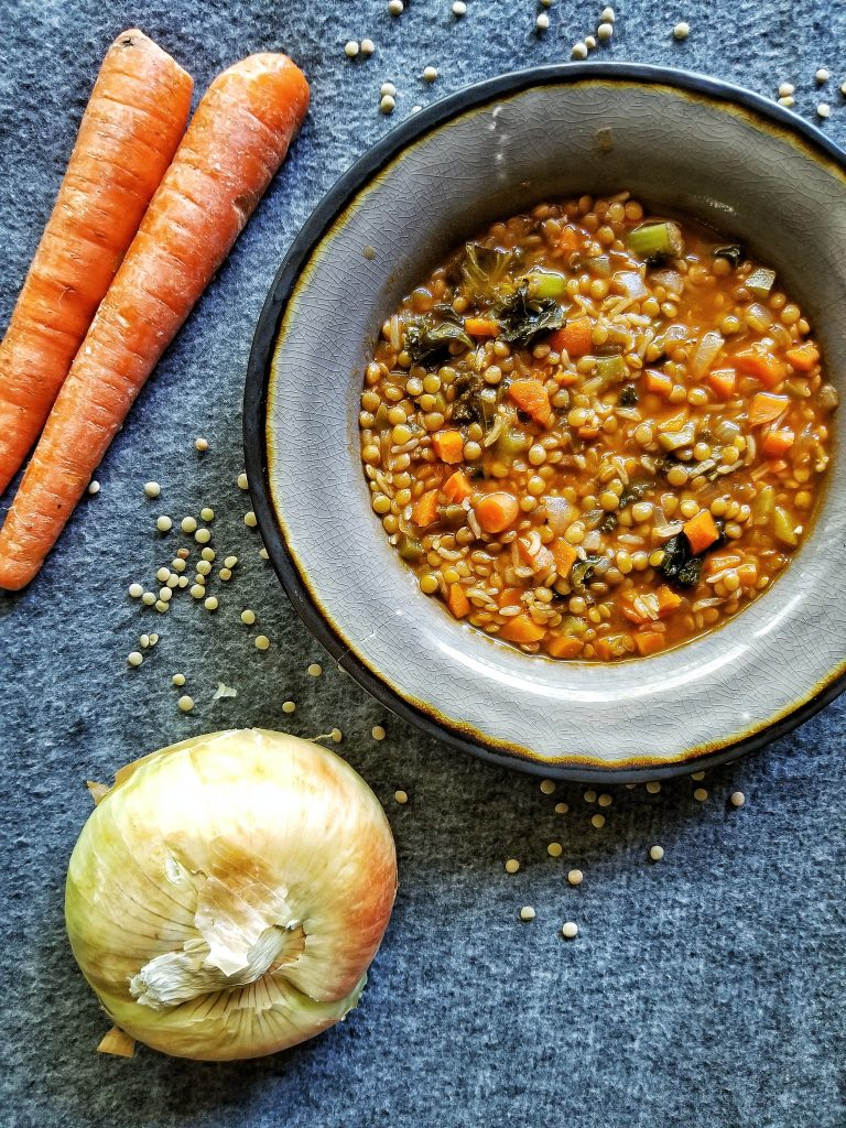 Bowl of vegetable soup with lentils, rice, and carrots.