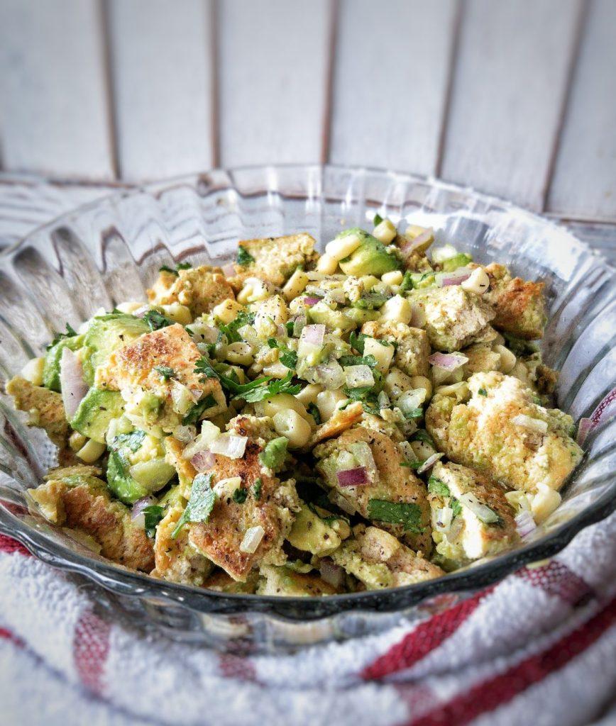 Large salad bowl with ripe avocado, tofu chicken, chopped onion, and fresh corn