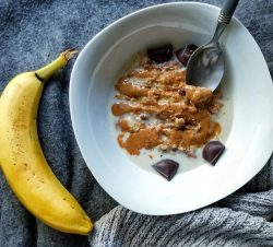 White bowl with oat bran topped with peanut butter and chocolate chunks