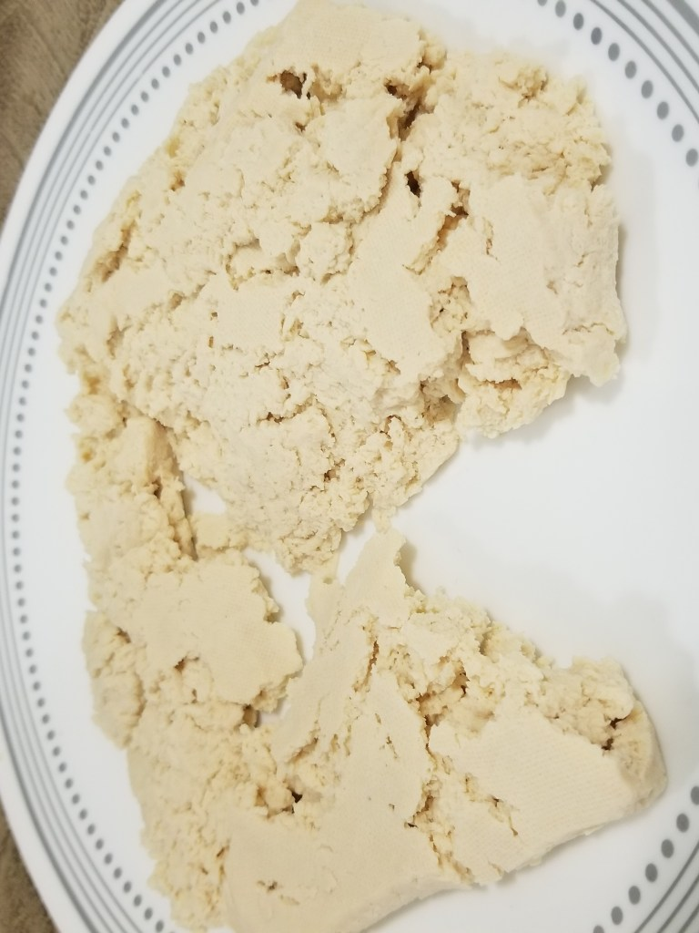A plate of tofu that has been thawed, drained, pressed, and pulled into chunks.