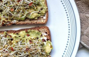 Avocado toast on whole wheat bread topped with sprouts and a pinch of red chili flakes