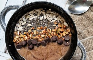 Coffee banana smoothie bowl topped with chia seeds, sunflower seeds, granola, chocolate chips, drizzle of honey