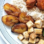 Puerto Rican food including rice, a serving of bean stew pan-fried tofu, and sweet plantains that have been pan-fried