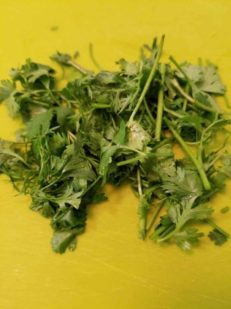 Roughly chopped cilantro on a chopping board