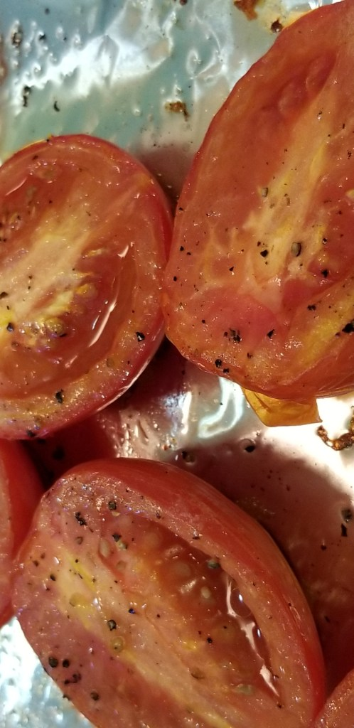 Roma tomatoes cut in half, roasted, on a baking tray lined with aluminum foil.