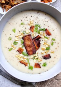 Creamy, garlic potato soup in a gray bowl topped with veggie mushroom bacon, green onions, and corn